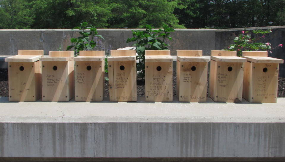 Eight birdhouses signed with names of students who built them in Westborough, Mass.