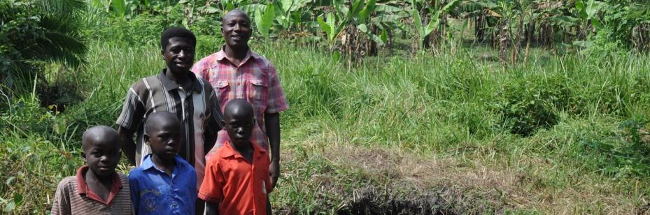 Ugandan family standing in front of spring where they collect water that Veolia has helped decontaminate.