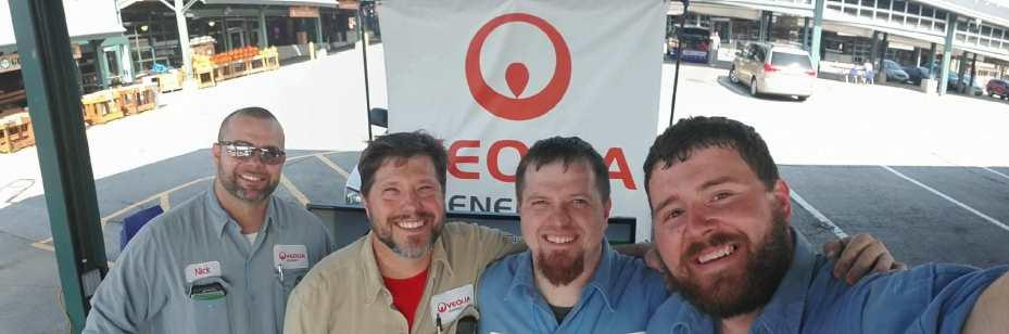 Four Veolia operations staff in front of Veolia booth at the Kansas City Green Fair.